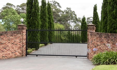Black wrought iron metal driveway entrance gates set in brick fence Stock Photo