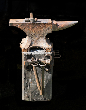 Medieval metal blacksmith anvil for forging weapons isolated on black