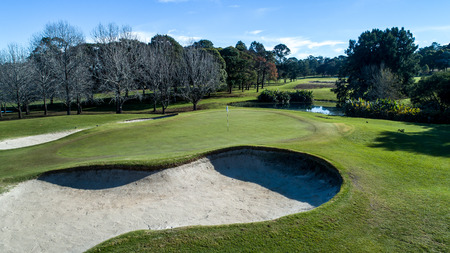 Golf course green with flag, bunkers and tree lined fairway