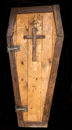 Historic convict made wooden coffin with cross isolated on black background