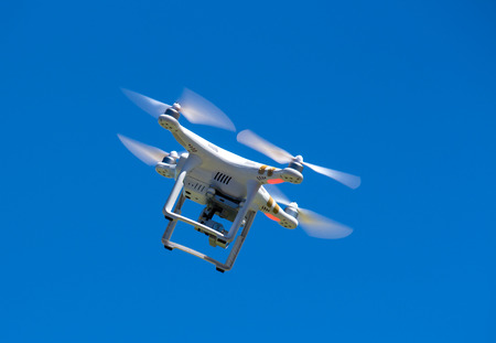 Drone or unmanned aerial vehicle in flight against blue sky Stock Photo
