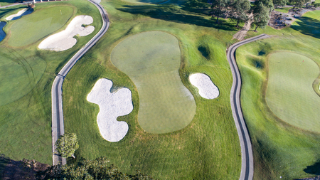 Aerial view of golf course green with flag, bunkers and golf cart pathways Stock Photo