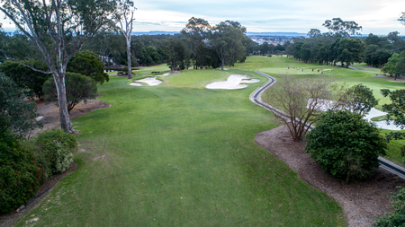 Golf course green with flag, bunkers and tree lined fairways in background