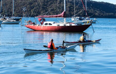 Two male kayakers paddling past boats moored on river
