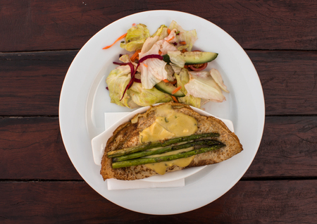 Chicken asparagus crepe with melted cheese served with salad on white plate