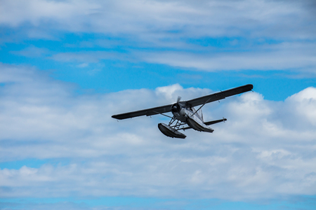 Seaplane in flight against blue cloudy sky Stock Photo