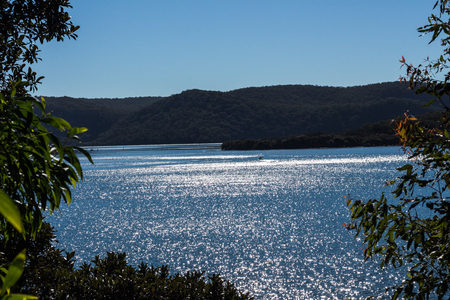 Shimmering sunlight on river against headland and blue sky