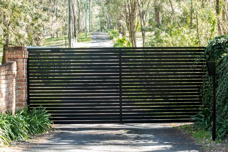 Black metal driveway entrance security gates set in brick fence