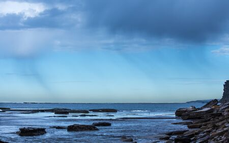 Coastal Rain falling over the ocean against blue sky with seaside rock ledge in foreground