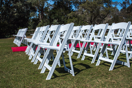 White ceremony chairs set up outdoors with red carpet aisle on green grass with trees in background Stock Photo