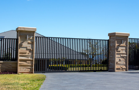 Black metal driveway entrance gates set in sandstone brick fence with residential garden in background