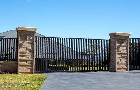 Puertas de entrada de entrada de metal negro en valla de ladrillo de piedra arenisca con jardín residencial en el fondo Foto de archivo