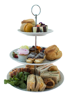 Assortment of high tea delicacies including sandwiches, scones, pies, sweet desserts isolated Stock Photo