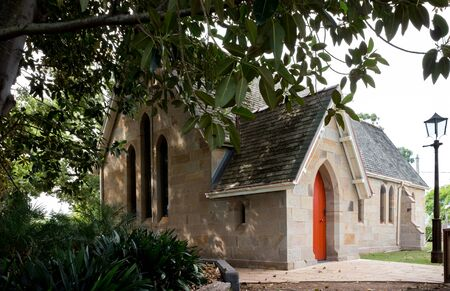 Historic sandstone brick country rural church in shade of large tree Stock Photo