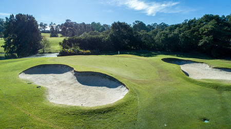 Aerial view of golf course green with sand bunkers on sunny day surrounded by trees