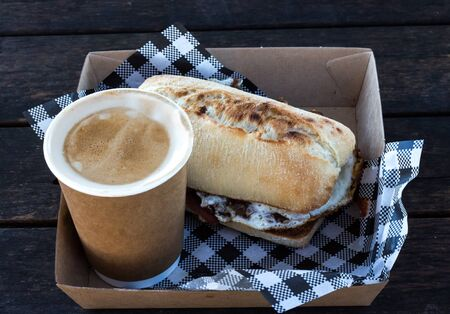 Bacon and egg breakfast ciabatta roll with take away coffee with checkered serviettes in box