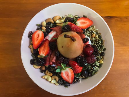 Poached pear and fresh berries granola breakfast cereal served in white bowl set on wooden table