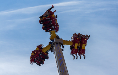 People riding high in the air on a carnival festival ride against blue sky Stock Photo