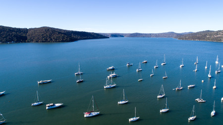 Aerial view of boats moored on Hawkesbury River, Brooklyn, Australia with blue water and headland in background Stock Photo
