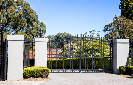 Black metal driveway entrance gates set in brick fence with garden trees in background