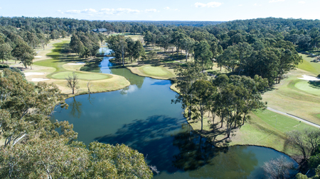 Aerial view of golf course fairways and green with flag, bunkers and dam water hazard surrounded by trees in background Imagens
