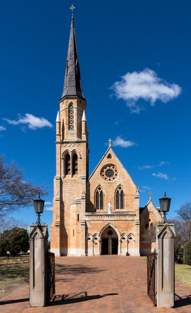 St Marys sandstone church with arched windows and tall steeple in Mudgee Australia against blue sky