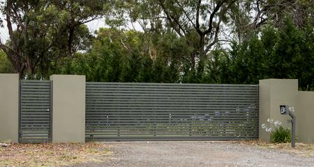 I cancelli dell'entrata della strada privata del metallo hanno messo in recinto del mattone che conduce alla proprietà rurale con gli eucalyptus nel fondo Archivio Fotografico - 92601172