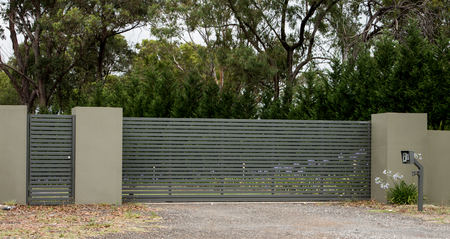 Metal driveway entrance gates set in brick fence leading to rural property with eucalyptus trees in background
