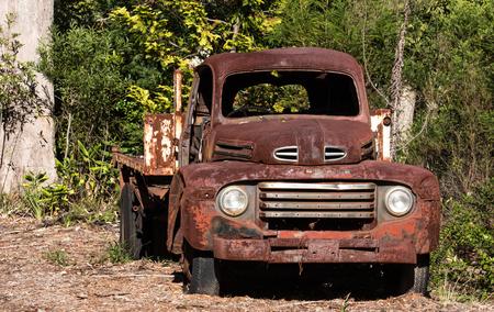 Vintage abandoned rusty farm truck ute against green trees 版權商用圖片 - 101976988