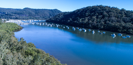 Aerial view of boats moored on Hawkesbury River, Brooklyn, Australia with blue water surrounded by eucalyptus gum trees in background