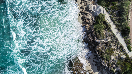 Aerial view ocean surf sea water washing onto sandy shoreline with stairs leading to beach
