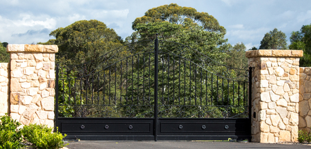 Metal driveway rural property entrance gates set in sandstone brick fence with eucalyptus gum trees in background