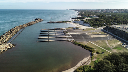 Aerial view Ocean Reef  boat harbour Perth Western Australia seaside coast waves rolling onto shore and stand up paddle boarders behind sea wall Фото со стока