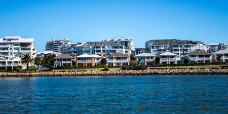 Australian waterside houses and condominiums with rock sea wall against blue sky Фото со стока