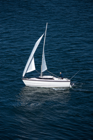 Solo sailor in small sailboat on blue water with reflection of white sails Фото со стока