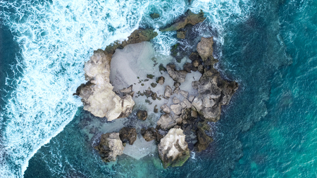 Aerial view of rocky outcrop near coastline showing waves rolling over rocks and sandy middle is home to seal colony