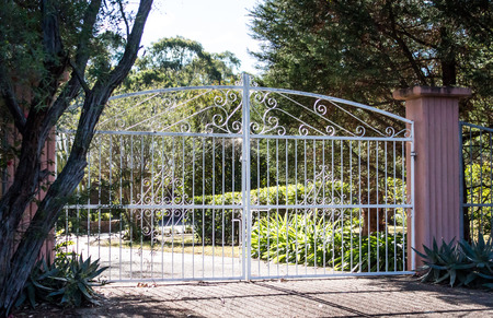 White wrought iron metal driveway entrance gates set in cement brick pillar with residential garden in background