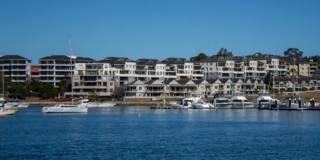Harbourside condominium apartment housing with boats floating on blue water against blue sky Reklamní fotografie