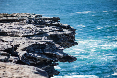 Oceanside rocky cliff top with blue coastal sea in background