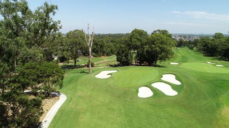Aerial drone view golf course green with sand bunkers, flag, trees, green grass against blue sky