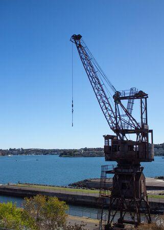 Industrial crane set dockside on Cockatoo Island Sydney Harbour Australia against blue water and sky