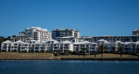 Harbourside condominium apartment housing with grass frontage against blue water and sky Фото со стока