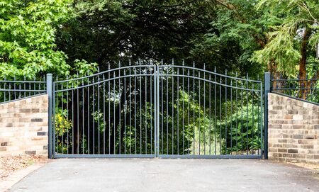 Metal driveway property entrance gates set in brick fence with garden trees  in background Фото со стока