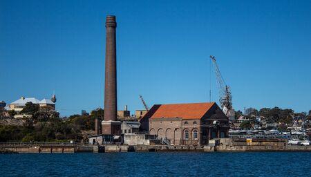 Factory brick smoke stack at historic dockyard and boat storage with crane against blue sky set on Cockatoo Island Sydney Harbour Australia Фото со стока
