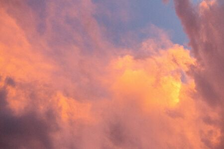 Pink, purple, orange golden glow of clouds at sunset against blue sky