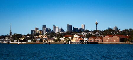City Harbourside houses, wharf and boat sheds on Sydney Harbour with city CBD skyline in background against blue sky Фото со стока