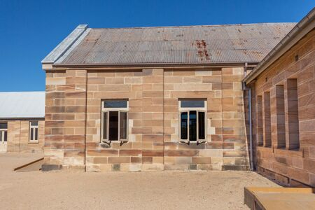 Sandstone convict brick made building with corrugated iron roof, open windows, pebbled courtyard against blue sky