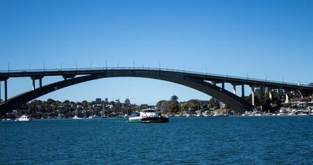 Gladesville Bridge spanning Parramatta River off Sydney Harbour with Rivercat Ferry travelling upstream, many pleasure boats on water against clear blue sky Фото со стока