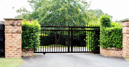 Black metal driveway property entrance gates set in brick fence with garden shrubs and trees in background Фото со стока
