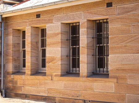 Sandstone convict brick made building close up of large tall windows and security grill Фото со стока